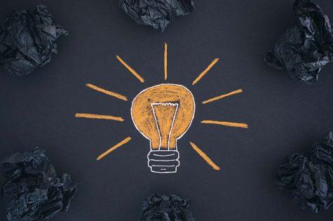 New Idea Concept. Drawing of a light bulb and black crumpled paper balls.